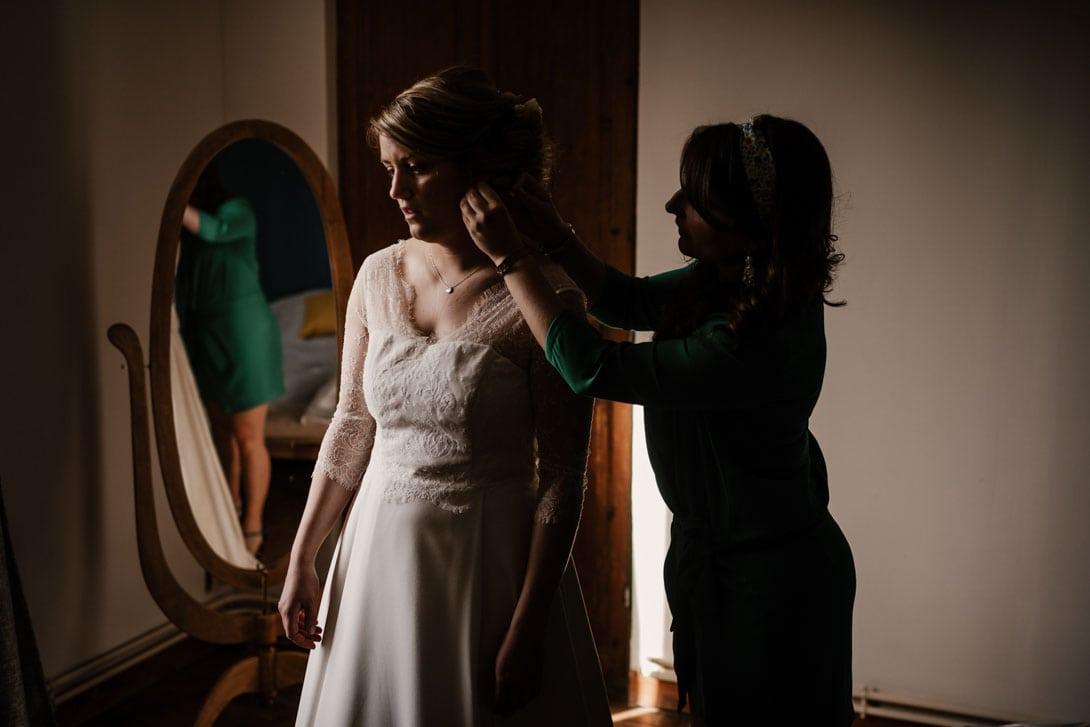 aide preparatif robe mariage par la temoin, elle lui met une boucle d'oreille