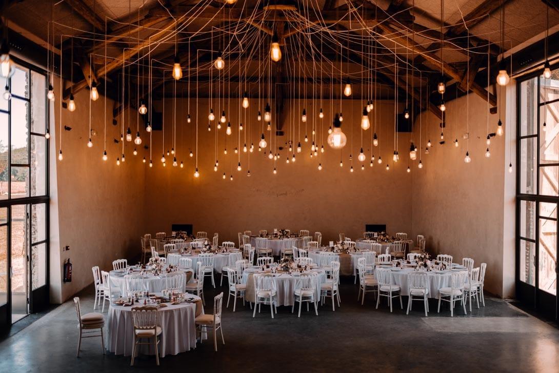 salle de la ferme d'armenon avec tables ronde et ampoules allumées au plafond