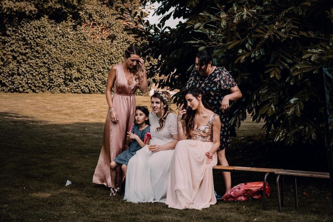 demoiselles d'honneur avec robes roses sur un banc avec la mariée