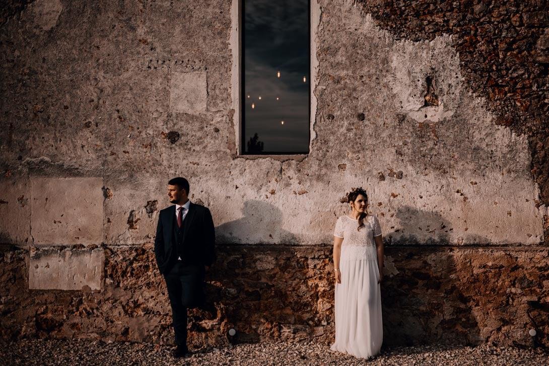 photo du couple de mariés devant une facade en pierre de la salle de la ferme d'Armenon