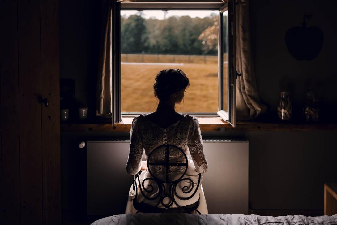 la mariée à la fenêtre après sa coiffure avant la cérémonie laïque