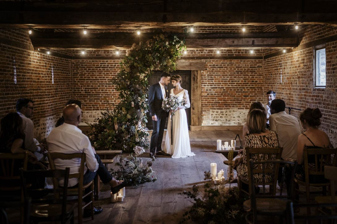 la cérémonie laïque du mariage avec arche de fleurs et végétation et chaises vintages