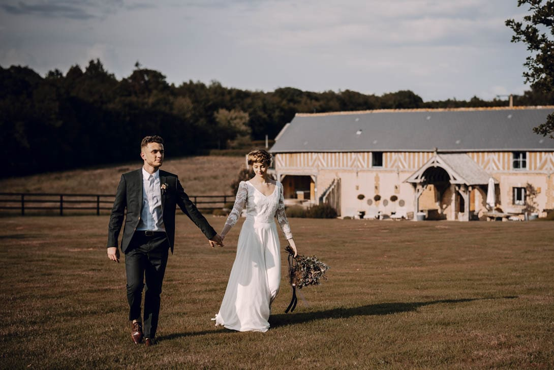 les mariée se baladant dans le champs du pré des colombiers, dans le calvados juste après la cérémonie de mariage