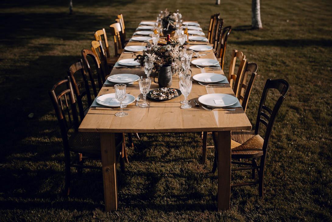 table de mariage dressée en bois, avec chaise vintage pour un mariage intime et vintage dans les prés sous les pommiers