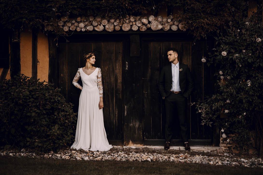 portrait des mariés devant la grande porte en bois du Pré des Colombiers lors de leur mariage intime en Normandie