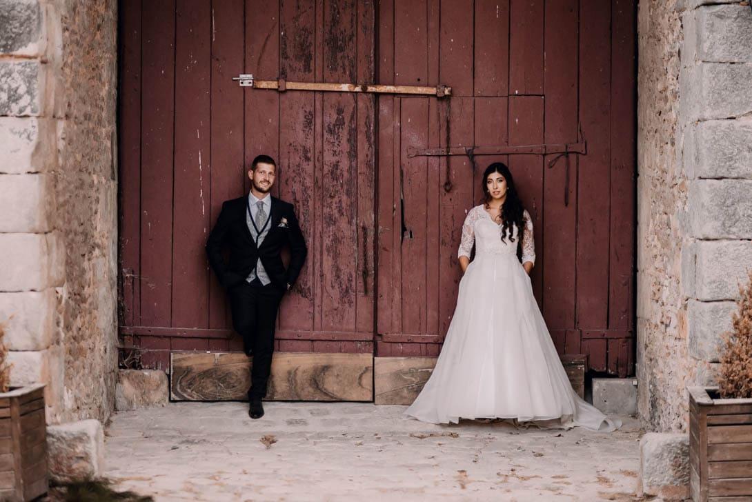 pose couple de marié devant une porte de ferme du lieu de réception de leur mariage