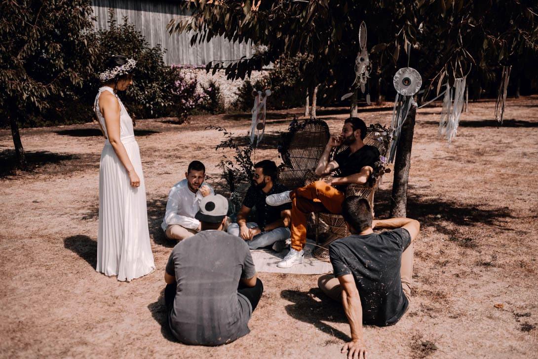 le marié et la mariée à l'ombre de l'arbre avec leurs amis et invités de leur mariage