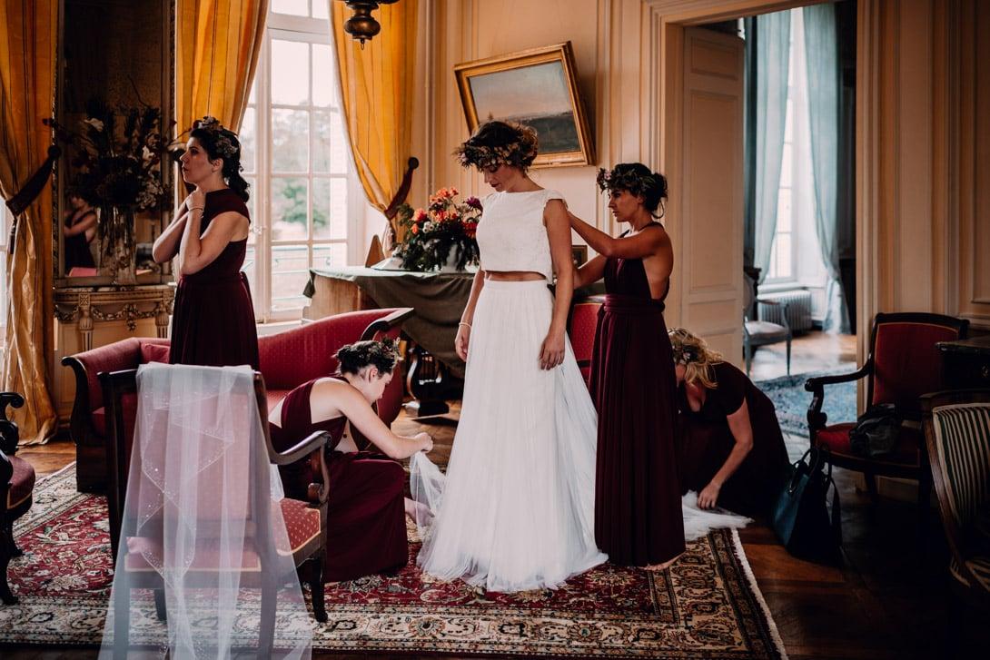 les demoiselles d'honneur aident la mariée à s'habiller pendant les préparatifs avant le mariage