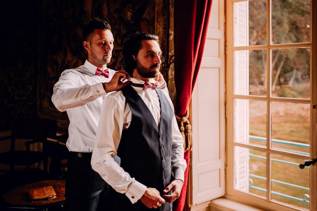 un des témoins du marié l'aide à fermer son nœud papillon