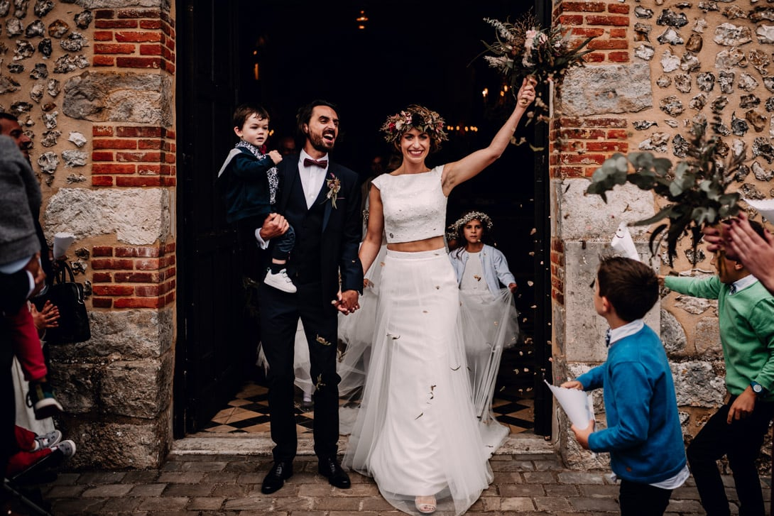 les mariés sortent de l'église sous les jets de pétales